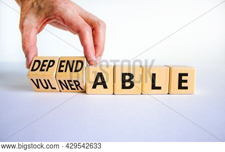 Vulnerable Or Dependable Symbol. Businessman Turns Wooden Cubes And Changes The Word Vulnerable To D