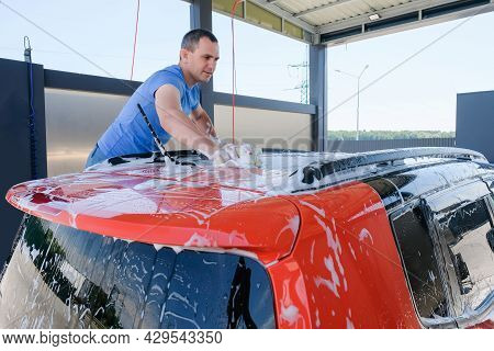 A Man Washes A Car At A Car Wash. The Car Is Covered With Foam