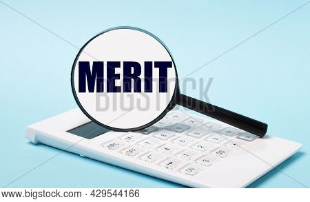On A Blue Background, A White Calculator And A Magnifying Glass With The Text Merit. Business Concep