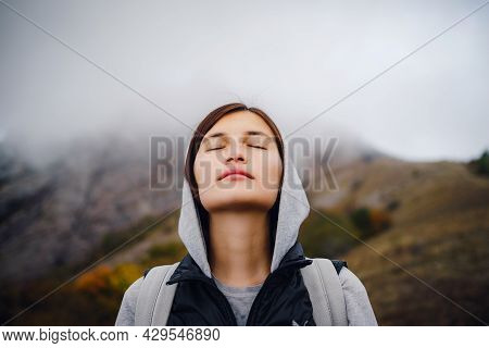 Asian Travel Woman Stands By The Mountain. Cold Weather, Fog On The Hills. Autumn Hike. The Beginnin