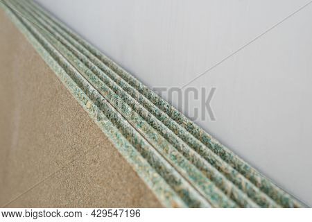 Several Sheets Of Moisture-resistant Chipboard Against A White Wall
