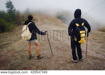 Two Man Friends With Backpack Hiking Together In Autumn Fog Nature. Male Backpacker Relax And Enjoy