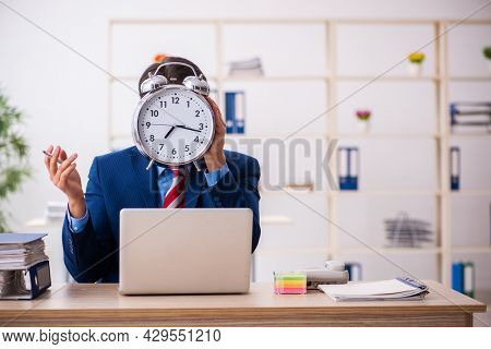 Young male employee in time management concept