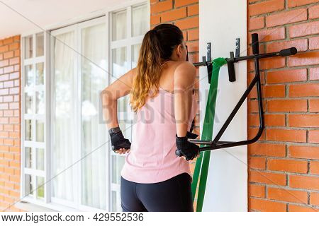 Young Woman Doing Triceps Dips On Parallel Bars At Home With Elastic Band