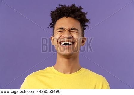 Close-up Portrait Of Happy Carefree Young Guy Laughing Loud, Chuckling Over Hilarious Joke, Bending