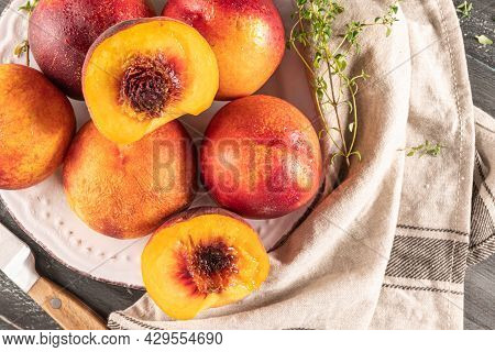 Ripe Peaches With Thyme Leaves In A Plate On A Wooden Board On A Background