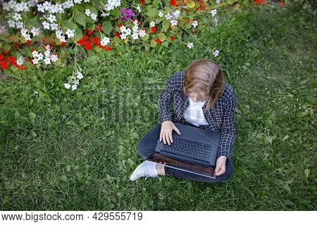 A Teenage Girl Is Working At A Laptop, Sitting In The Garden On The Grass Among Flowers And Looking