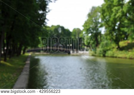 Blurry, Defocused View Of The City Pond And Bridge. Defocused Trees. Summer Sunny Day.