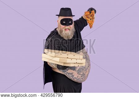 Funny Plump Man In Hero Suit Holds Boxes And Pizza Slice On Purple Background