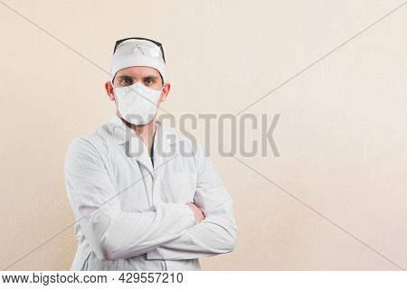 Young Doctor In Wshite Lab Coat, Protective Glasses And Protective Breathing Mask With His Hands On