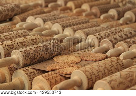 A Display Of Wooden Rolling Pins With Various Designs And Sample Cookies.