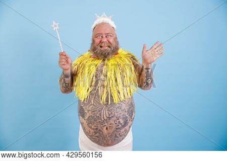 Joyful Bearded Plump Man With Crown, Magic Stick And Yellow Cape On Light Blue Background