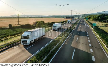 Convoy Opf White Transportation Trucks Passing By On A Country Highway At A Bright Sunny Day. Busine
