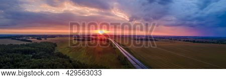 Beautiful Winding Road Leading Through Rural Countryside With Evening Sunlight. Dramatic Sky Backgro