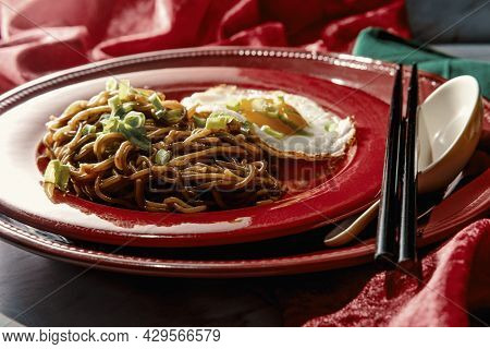 Japanese Spicy Ramen Noodles Served With Fried Sunny Side Up Egg And Sliced Scallion Garnish