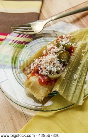 Mexican Steamed Chili And Cheese Masa Tamales Wrapped In Corn Husk Topped With Spicy Tomato Salsa An