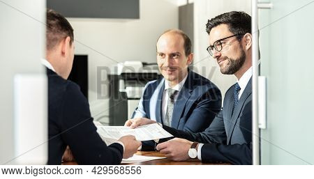 Group Of Confident Successful Business People Reviewing And Signing A Contract To Seal The Deal At B