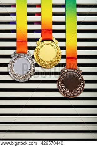Set Of Gold Silver And Bronze Award Medals Hanging Up Vertical Composition