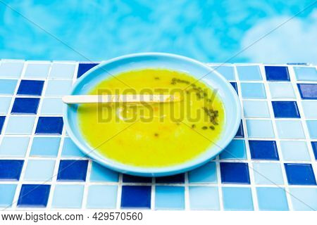 Melted Passion Fruit Popsicle In Front Of A Swimming Pool