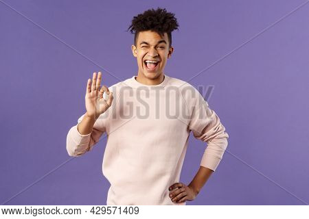 Portrait Of Enthusiastic Young Relaxed Man Show No Problem, Guarantee Gesture, Recommend Awesome Cou