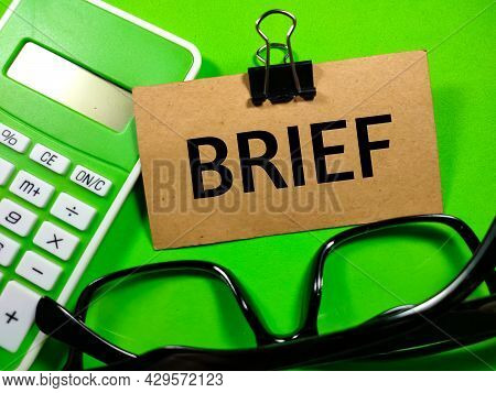 Business Concept.text Brief Writing On Brown Card With Calculator And Glasses On A Green Background.