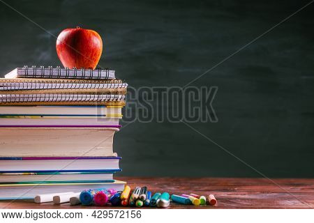 Pile of book and exercise books with shool applies and apple snack with chalkboard.  Back to school concept.