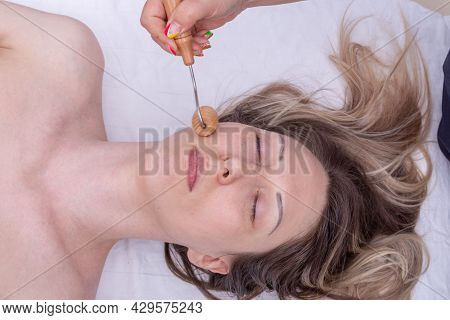 Madero Therapy, Anti-aging Relaxing Massage - Hands Massaging The Girls Cheek Using A Natural Wooden