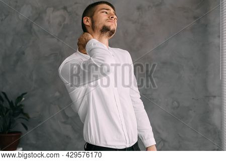 Workplace Businessman Suffering From Neck Pain While Working From Office. An Overworked Young Worker