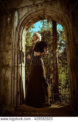 Full length portrait of black widow. An aristocratic old widow woman with beautiful gray hair and a rich black dress stands sad in the arch of the castle. Fantasy World. Halloween.