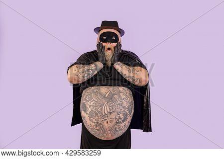 Shocked Plump Man In Hero Costume Holds Cheeks Standing On Purple Background