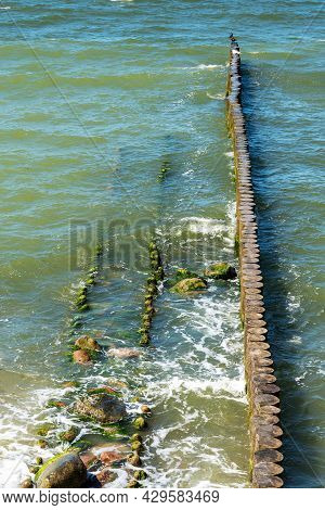 A Breakwater Made Of Logs Cuts Through The Sea Wave
