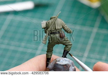 Scale Modeling. A Man Painting Shoes On A Plastic Model Of A Soldier Close Up. Wwii Soldier Figure 1