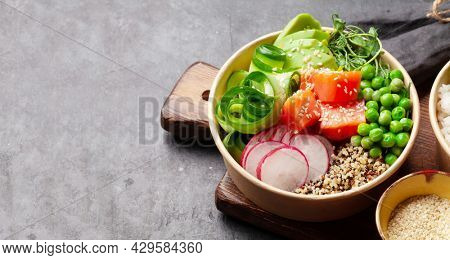 Poke bowl with salmon, cucumber and avocado. Traditional hawaiian meal. With copy space