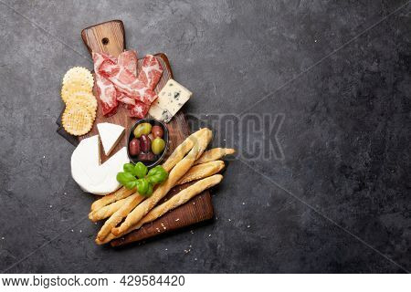 Cheese, meat and olives antipasto. Appetizer selection on wooden board. Top view with copy space. Flat lay