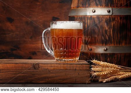 Mug of light lager beer and old wooden barrel. With copy space