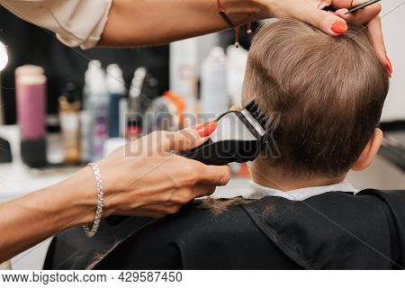 Shooting In A Beauty Salon. A Barber Makes A Haircut For A Little Boy With A Machine