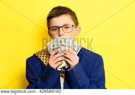 Not A Lot Of Adult Child, Financially Literate Boy, Money In The Hands Of A Child, Portrait On A Yel