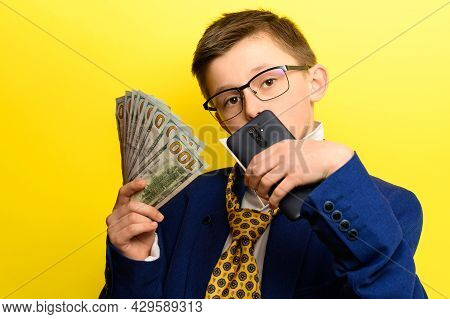 Boy In An Adult Suit On A Yellow Background, International Currency In The Hands Of A Child, Childre