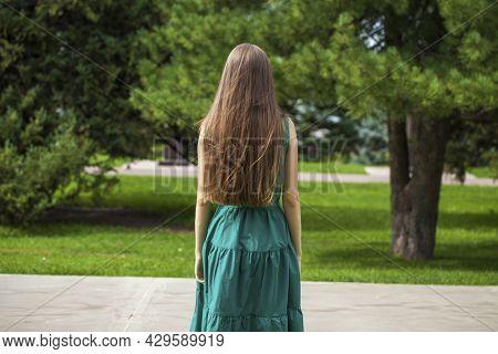 Blonde hair model. Back view blonde girl, summer park outdoor