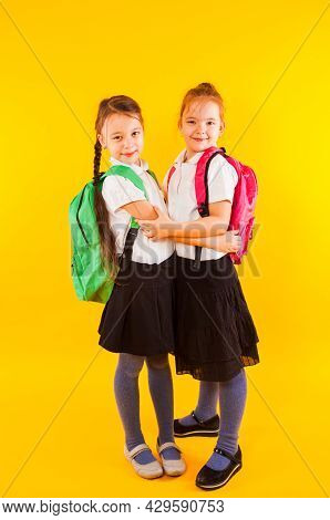Two Girls Classmates Are Hugging On A Yellow Background