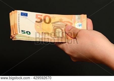 Euro In The Hands Of A Man On A Black Background, Transferring And Receiving Money As A Reward For W