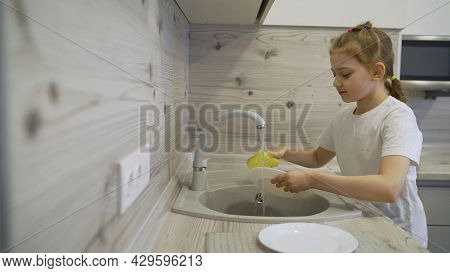 Little Girl Talking On The Phone In The Kitchen. She Stands At The Table And Is Enthusiastically Tal