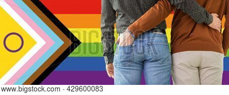 lgbtq, trans and intersex rights concept - close up of male gay couple hugging over progress pride flag on background