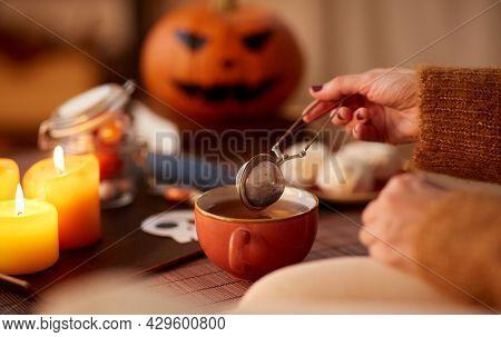 drinks, holidays and leisure concept - woman's hand with mesh tea infuser ball and mug at home on halloween