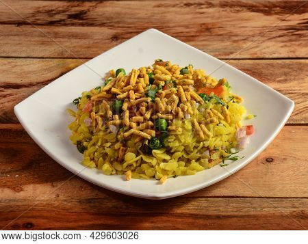 Poha, Made With Flattened Rice, Typically Western Indian Breakfast, Served In A Plate Over A Rustic