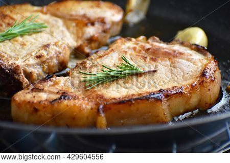 Pork Chop On A Frying Pan. Grilled Pork Steak With Garlic And Rosemary On A Black Metal Pan.