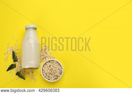 Vegan Milk And Oat Flakes On Yellow Background, Flat Lay. Space For Text