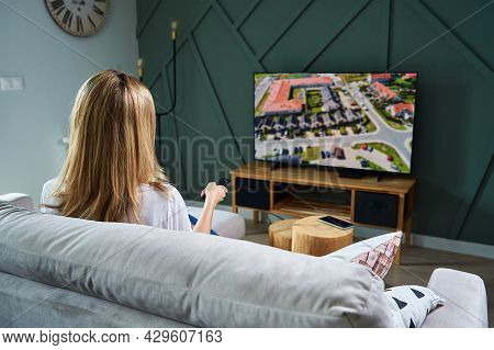 Woman Resting At Home. Person Watch Tv Set On The Sofa And Switch Channels With Remote Control