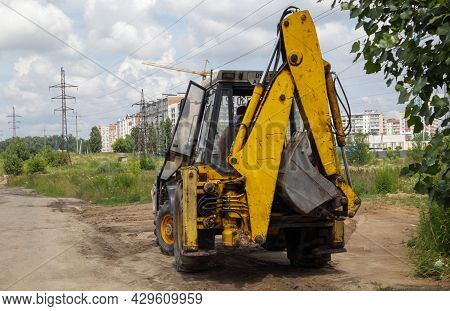 Excavator On A Construction Site Against The Background Of The Sky. Heavy Machinery At Work. A Large