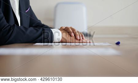 Man In An Elegant Suit Put His Hands On A Wooden Table Next To A Sheet Of Paper And A Fountain Pen.